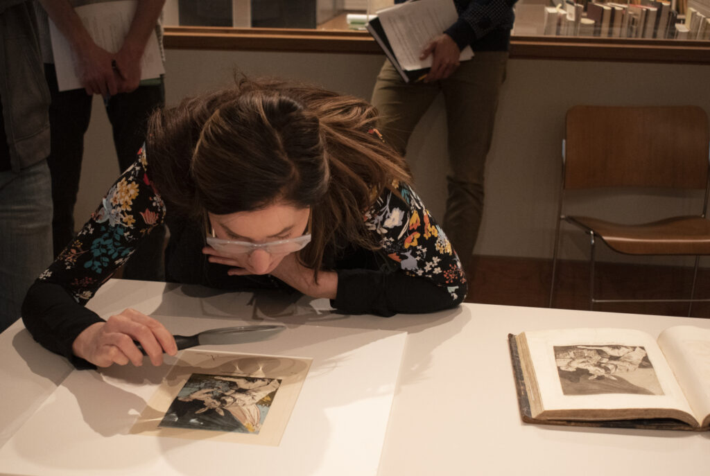 woman examining piece of art