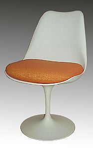 Photograph of mid-century chair with white back and pedestal and orange seat cushion.
