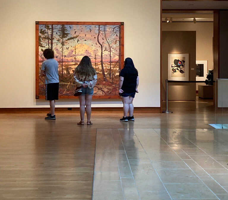 Visitors looking at painting